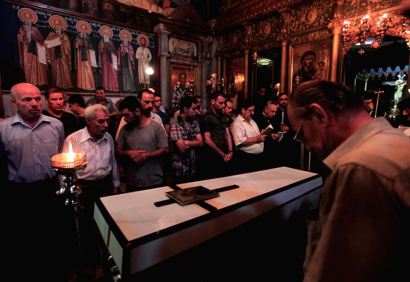 Relatives and friends of Palestinian Jalila Ayad, a Christian woman whose body was found under the rubble of her home after an Israeli airstrike, mourn over her coffin