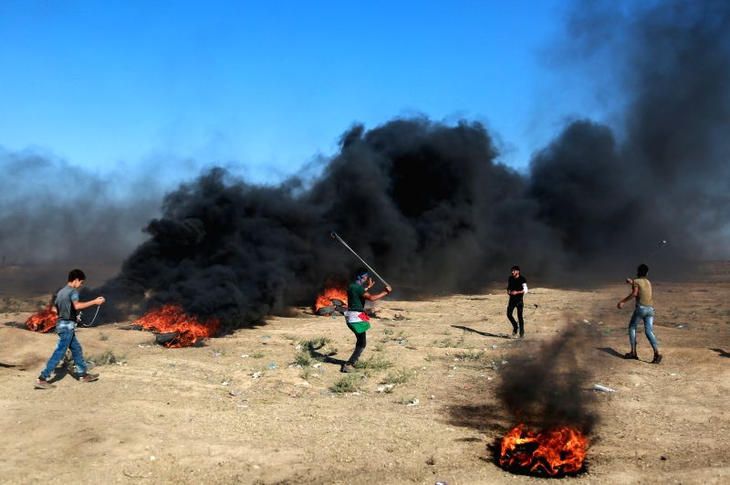 GAZA, July 27, 2018 - A Palestinian protester hurls stones at Israeli troops during clashes on the Gaza-Israel border, east of Gaza City, on July 27, 2018. Two Palestinians were killed on Friday in ...