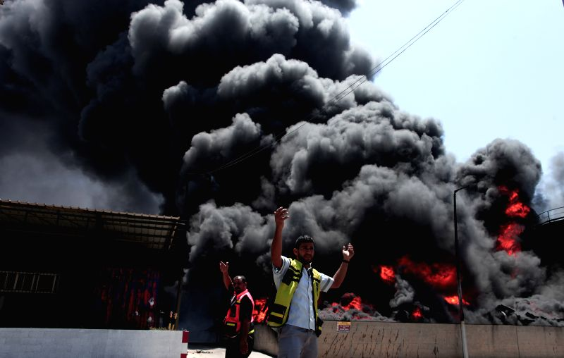 Palestinian firefighters react as flames engulf the fuel tanks of the main power plant which supplies electricity to the Gaza Strip, in Gaza City on July 29, 2014. ...