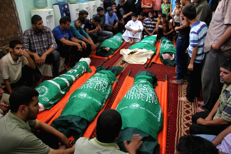 Palestinian Mourners gather around the bodies of six members of al-Hashash family, who were killed in an Israeli air strike on their home, during the funeral in the ...