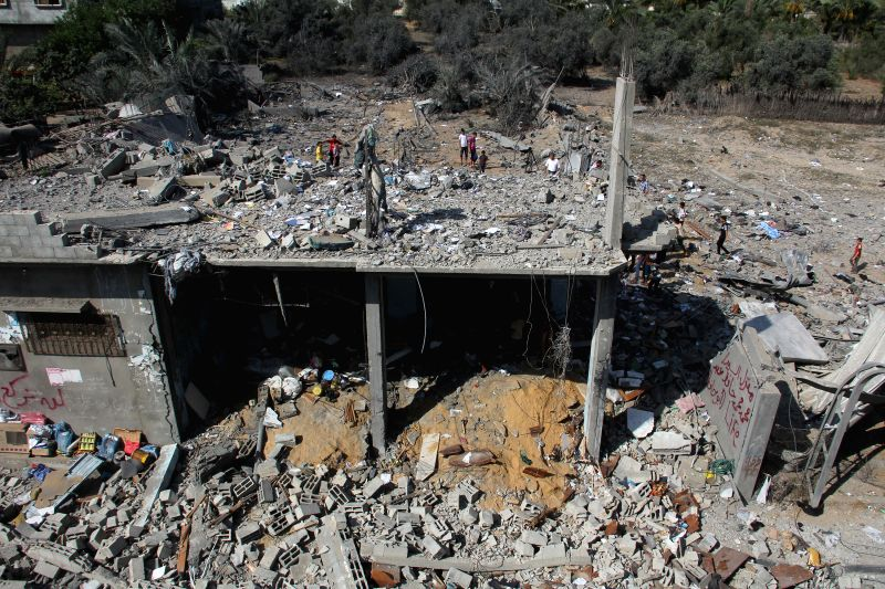 Palestinians inspect the rubble of a destroyed building following an Israeli military strike in the southern Gaza Strip city of Khan Yunis, on July 8, 2014. An Israeli .