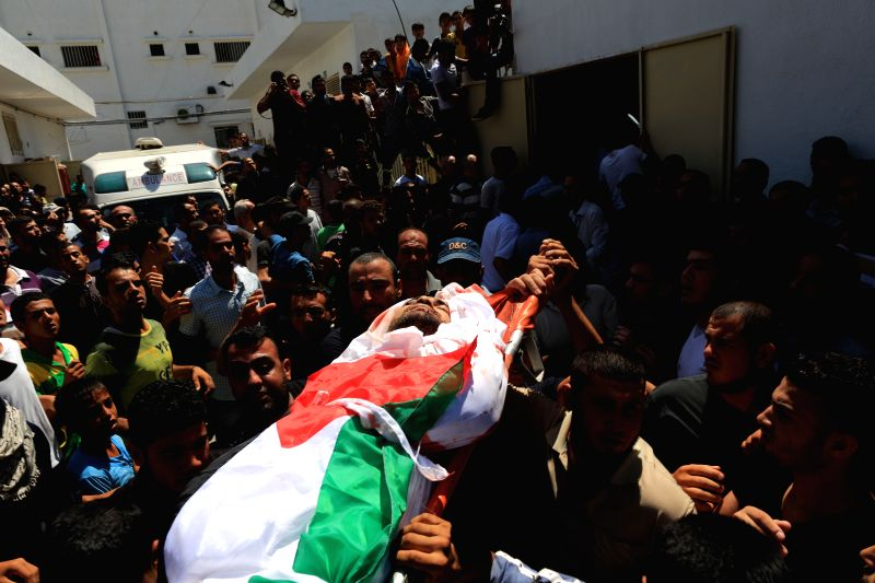 Palestinians carry the body of a member of a Hamad family during their funeral in the northern Gaza Strip town of Beit Hanun, on July 9 2014. Six members of a Hamad ...