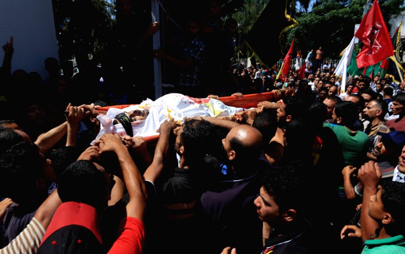 Palestinians carry the body of a member of a Hamad family during their funeral in the northern of Gaza Strip town of Beit Hanun, on July 9 2014. Six members of a Hamad .
