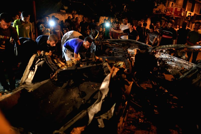 Palestinians gather around the remains of the car which police said was targeted in an Israeli air strike in Gaza City, July 9, 2014. The death toll of the Palestinians