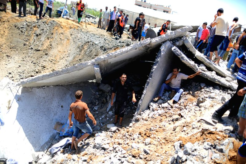 People search the rubble for body of a Palestinian boy whom hospital officials said was killed in an Israeli air strike on his family's house, in Gaza city, July 9, ...