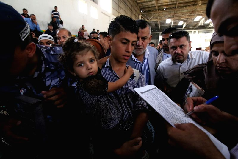 GAZA, June 1, 2016 - A Palestinian boy waits with his sister for a travel permit to cross into Egypt through the Rafah border crossing, in the southern Gaza Strip, on June 1, 2016. The Egyptian ...