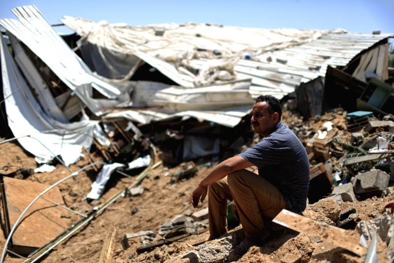 A Palestinian sits on the rubble of a destroyed metal workshop after it was hit by an Israeli airstrike in Gaza City, early Tuesday, June 17, 2014. Israeli warplanes ..