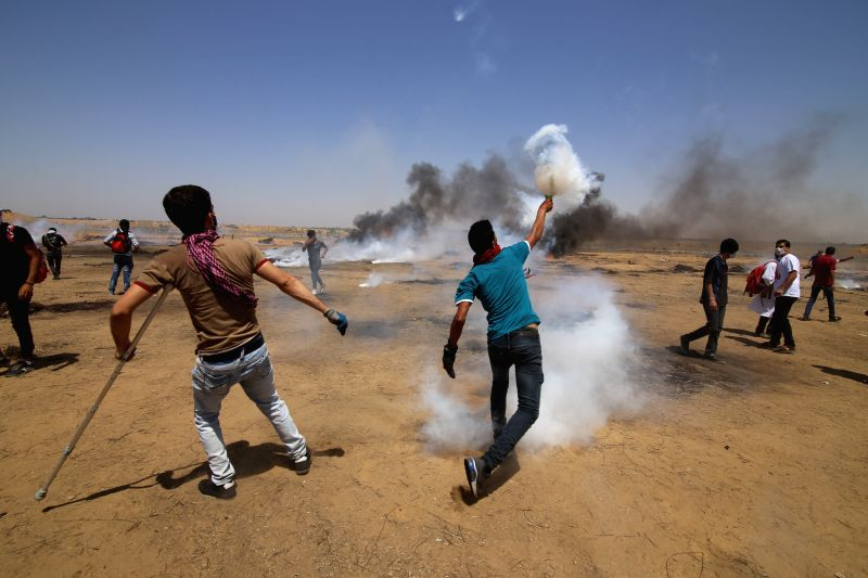 GAZA, June 8, 2018 - A Palestinian protester throws back a tear gas canister at Israeli troops during clashes with Israeli troops, on the Gaza-Israel border, east of the southern Gaza Strip City of ...