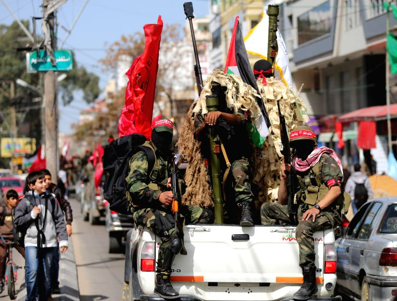 Palestinian militants from the Democratic Front for the Liberation of Palestine (DFLP) hold weapons as they take part in a rally marking the 46th anniversary of the ...