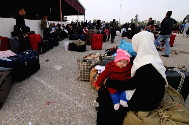 A Palestinian woman, hoping to cross into Egypt, holds a baby as she waits at the Rafah crossing point between Egypt and the southern Gaza Strip, March 10, 2015. ...