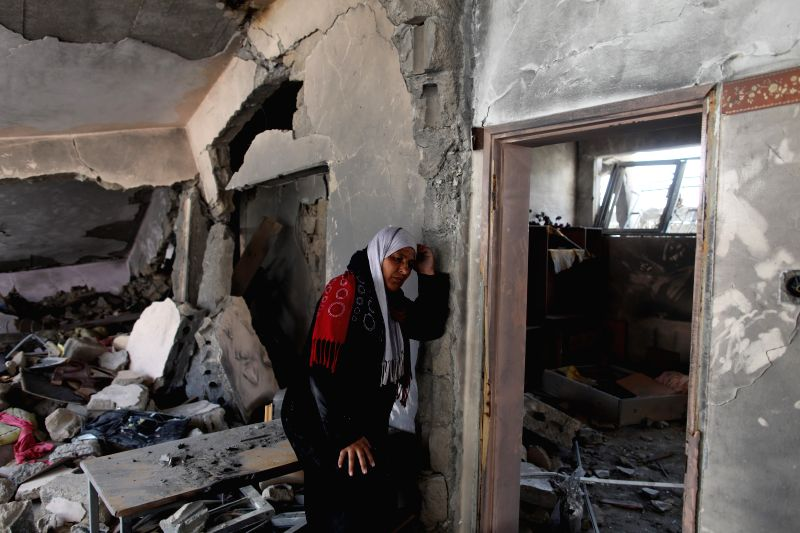 A Palestinian woman stands in her house destroyed by Israeli military forces in the northern Gaza Strip town of Beit Hanoun, on Aug. 4, 2014. Since the beginning .