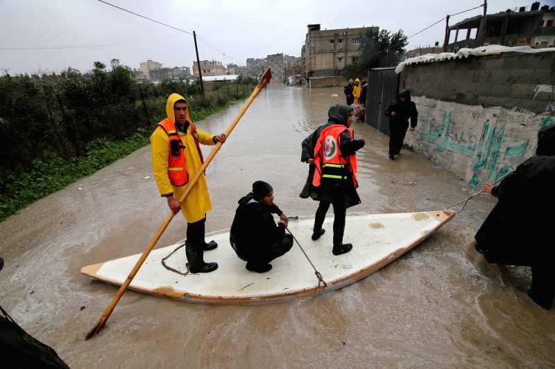 A Palestinian rescue worker (L) paddles a raft on a flooded street to evacuate a resident in the southern Gaza Strip city of Rafah, Jan. 9, 2015. Rescuers have ...