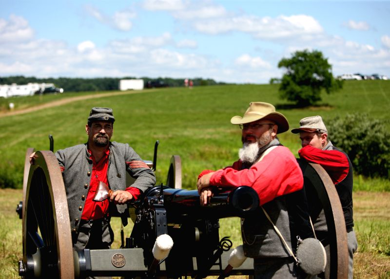 Forty-six-year-old Jim Plummer from Baltimore (L), playing Confederate soldier, stands by a cannon during reenactment activities marking the 151st anniversary of .