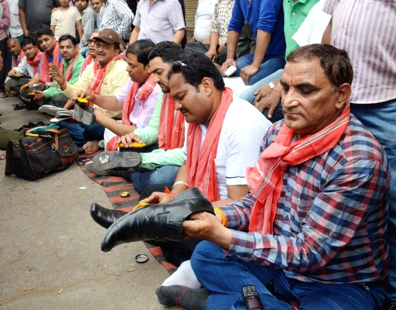 Ghaziabad jewellers polish shoes to protest against the one percent excise duty proposed by Finance Minister Arun Jaitley in the 2016-17 national budget, in Ghaziabad, on April 5, 2016. - Arun Jaitley