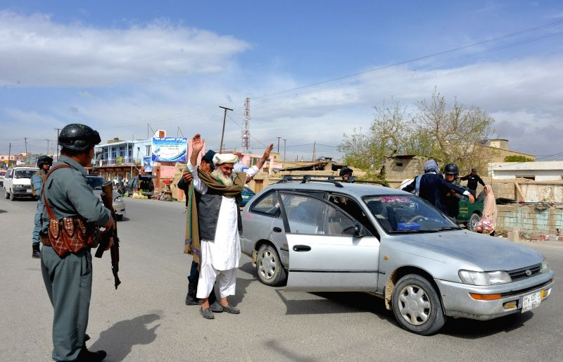 Afghan policemen search passengers at a police checkpoint in Ghazni province, east Afghanistan, April 18, 2015. Some five civilians have been shot and killed in the ...
