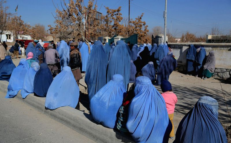 Afghan women wait to receive winter relief goods distributed by Afghan government in Ghazni, east Afghanistan, Dec.15, 2014.