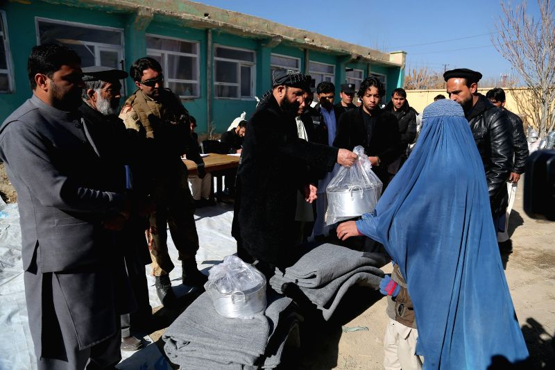 An Afghan woman receives winter relief goods distributed by Afghan government in Ghazni, east Afghanistan, Dec.15, 2014.