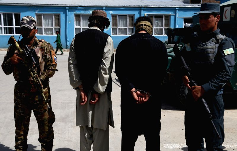 GHAZNI, July 14, 2018 - Suspected militants (C) stand handcuffed in Ghazni city, capital of Ghazni province, Afghanistan, July 14, 2018. Afghan security personnel captured two suspected militants ...