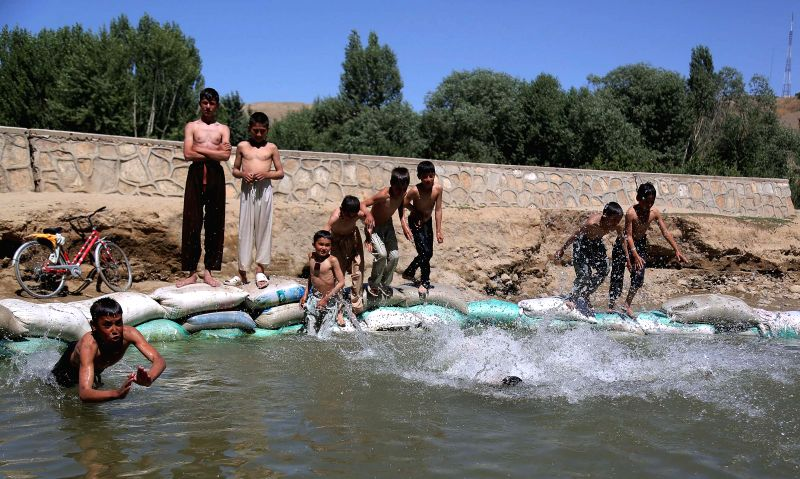Afghan children cool themselves in a canal in Ghazni province, eastern Afghanistan, on July 19, 2014.