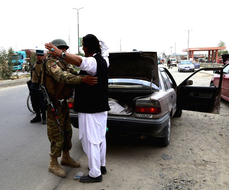 GHAZNI, July 21, 2018 - An Afghan security force member checks a man at a security checkpoint in Ghazni province, Afghanistan, July 21, 2018. At least two security personnel including a district ...