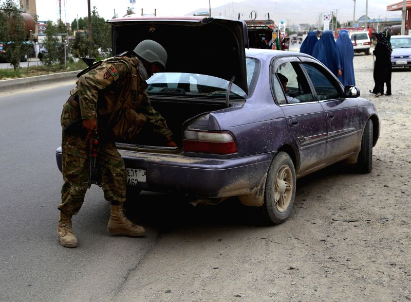 GHAZNI, July 21, 2018 - An Afghan security force member checks a vehicle at a security checkpoint in Ghazni province, Afghanistan, July 21, 2018. At least two security personnel including a district ...