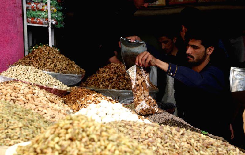 GHAZNI, June 14, 2018 - An Afghan shopkeeper prepares dry fruit ahead of Eid al-Fitr festival in Ghazni city, capital of Ghazni province, eastern Afghanistan, June 13, 2018. Afghan Muslim families ...