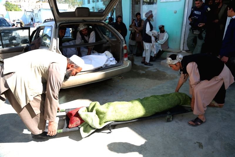 Afghans carry a dead body into a vehicle after Taliban attack in eastern Ghazni province of Afghanistan on May 12, 2014. Earlier on Monday, more than 300 Taliban, ...