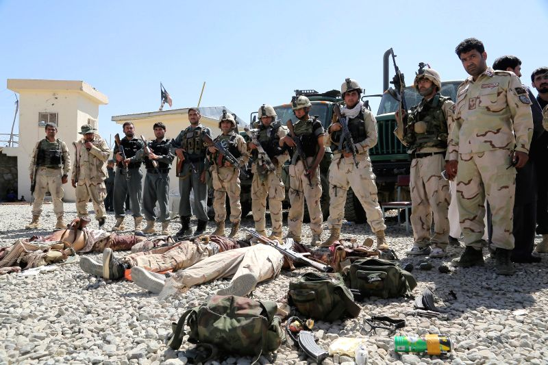 Afghan security forces stand around bodies of Taliban militants at the site of an attack in Ghazni province in eastern Afghanistan, Sept. 4, 2014. At least 24 people