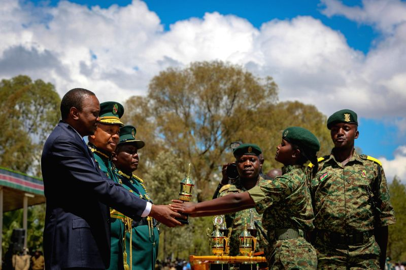 GIL GIL (KENYA), April 24, 2015 Kenyan President Uhuru Kenyatta (L) presents a trophy to a graduate of the National Youth Service (NYS) Gil Gil college, during a graduation ceremony in ...