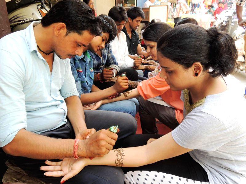 Girls applying hena on the eve of Raksha Bandhan in Gurgaon on Aug. 9, 2014.