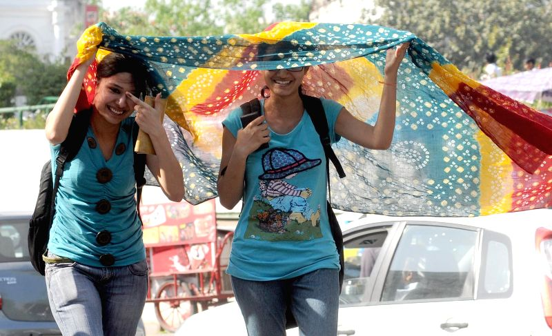 Girls cover their heads with a dupatta to shield themselves from sun in New Delhi on April 11, 2014.