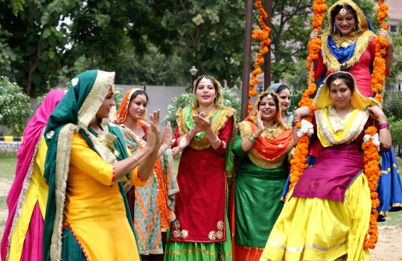 Girls enjoy on a swing ahead of Teej festival in Amritsar, on Aug 10, 2018.