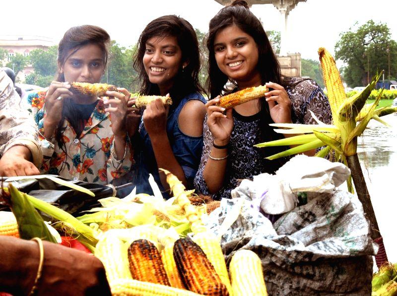 Girls enjoy roasted corn during rains, in Jaipur on July 16, 2018.
