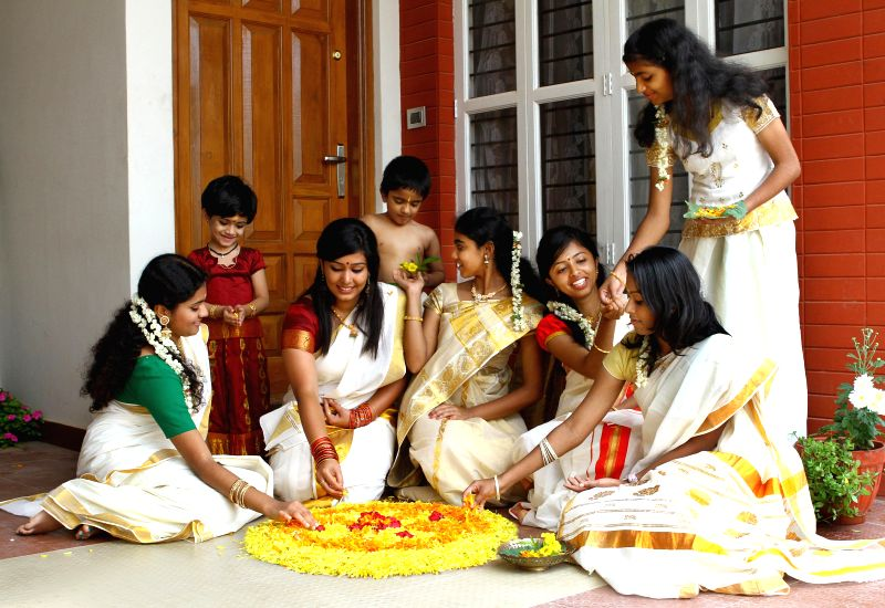 Girls from Kerala making Pookkalam (Floral Art) in front of their residence to celebrate Onam festival on Monday in Bangalore on Sept. 14, 2013.