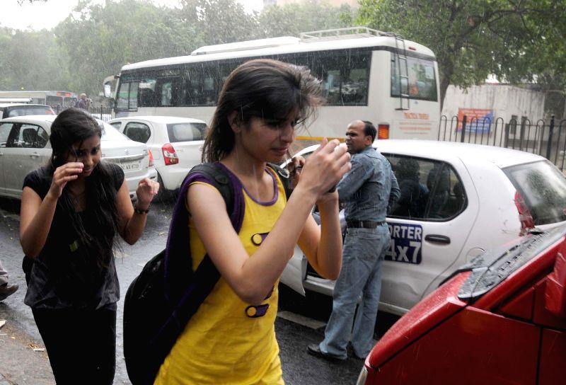 Girls get wet during sudden rain in New Delhi on  May 5, 2014.