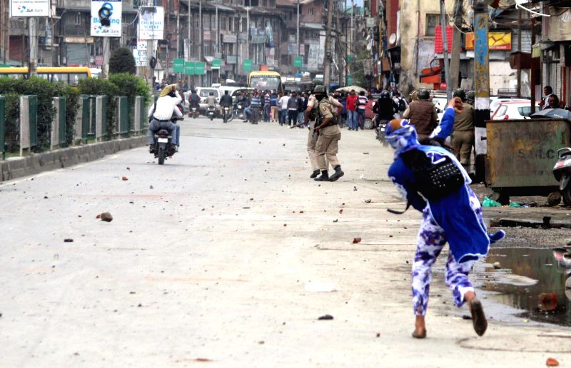 Girls pelt stones on security personnel during a protest in Srinagar.