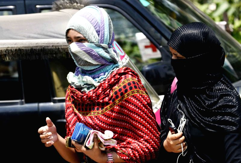 Girls protect themselves from the scorching heat on a hot day in Patna on May 10, 2014.