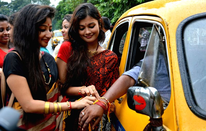 Girls tie friendship bands to a taxi driver in Kolkata on Aug 7, 2016.