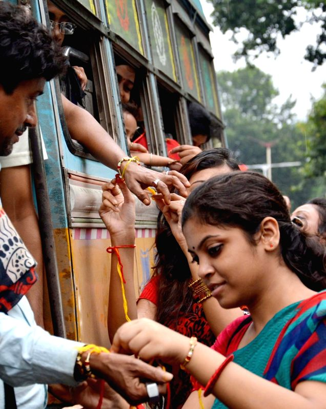 Girls tie friendship bands to people in Kolkata on Aug 7, 2016.
