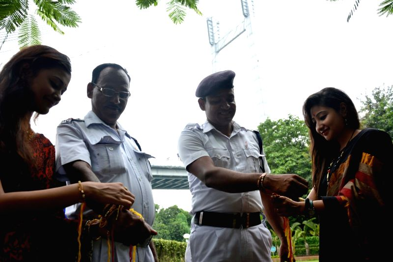 Girls tie friendship bands to policemen in Kolkata on Aug 7, 2016.