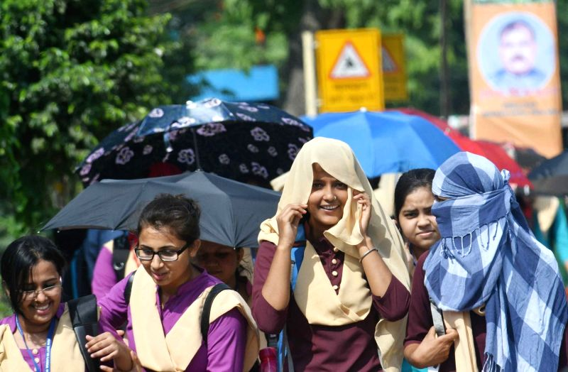 Girls use umbrella and scarfs to shield themselves from scorching sun on a hot day,in Patna, on July 13, 2018.