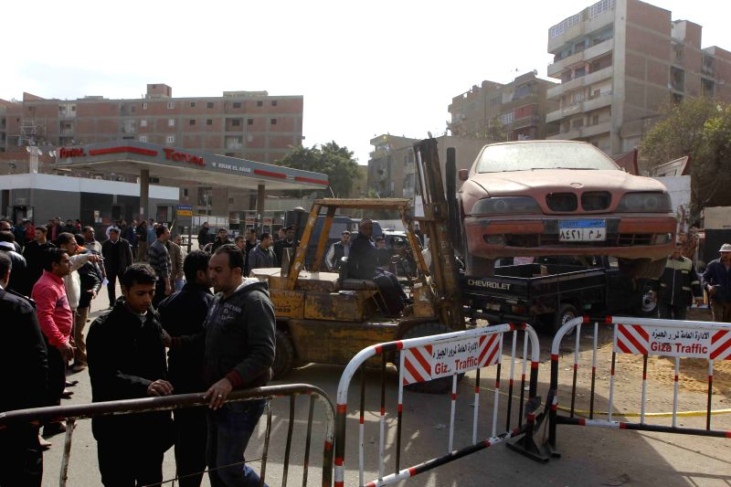 A forklift moves a destroyed car in a bomb explosion site outside Waraq police station in Giza, Egypt, on Feb. 26, 2015. At least one was killed and several others ...
