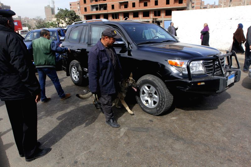 Policemen check cars near a bomb site outside Waraq police station in Giza, Egypt, on Feb. 26, 2015. At least one was killed and several others wounded on Thursday in ...