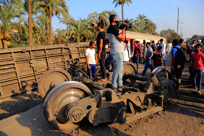 GIZA, July 13, 2018 - People gather at the accident site where a train derails in Giza, Egypt, July 13, 2018. At least 55 people were injured as an Egyptian train derailed on Friday near Giza, south ...