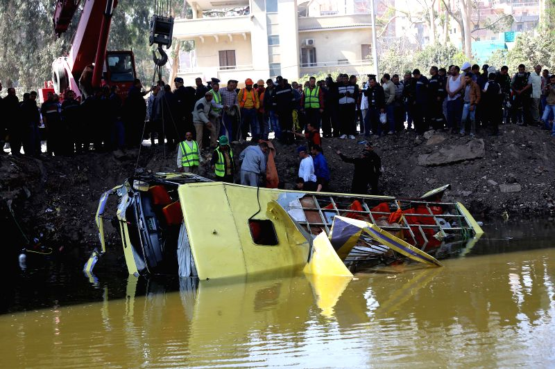 People watch the accident scene along a canal in Giza, Egypt, on March 21, 2015. At least nine people were killed Saturday after a bus fell into the canal in Egypt's ...