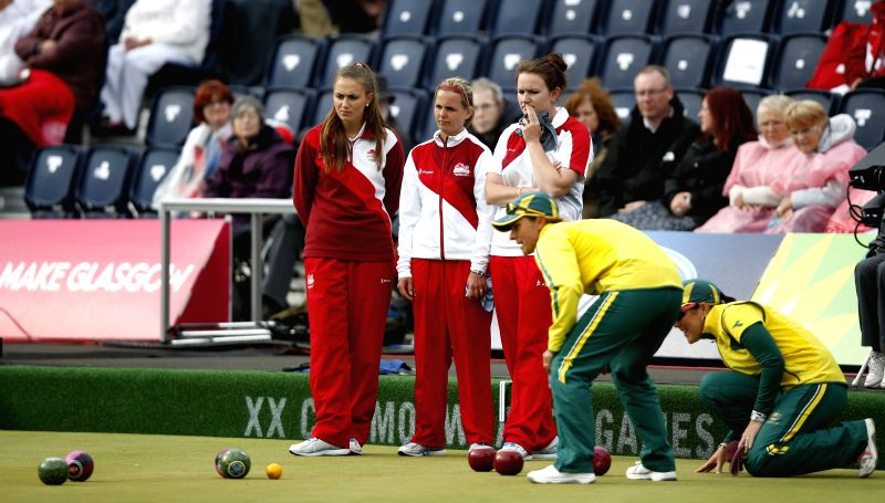 Sophie Tolchard, Ellen Falkner and Sian Gordon (1st L to 3rd L) of England look on during the women's triples gold medal match of Lawn Bowls between England and ...