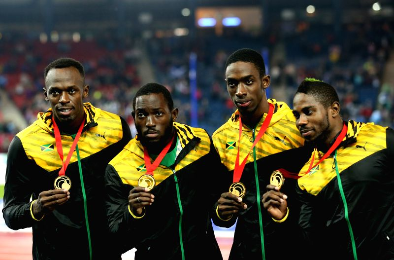 Athletes of Jamaica react during the awarding ceremony for the men's 4X100m relay final of Athletics at the 2014 Glasgow Commonwealth Games in Hampden Park in ...
