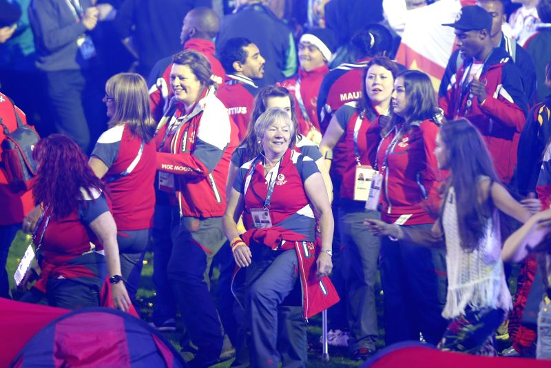 Volunteers dance during the closing ceremony for the Glasgow 2014 Commonwealth Games at the Hampden Park in Glasgow, the United Kingdom, on Aug. 3, 2014. ...