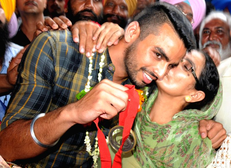 Glasgow Commonwealth Games 2014 bronze medal winner in men`s triple jump event athlete Arpinder Singh is welcomed by his mother on his arrival in Amritsar on Aug. 9, 2014.