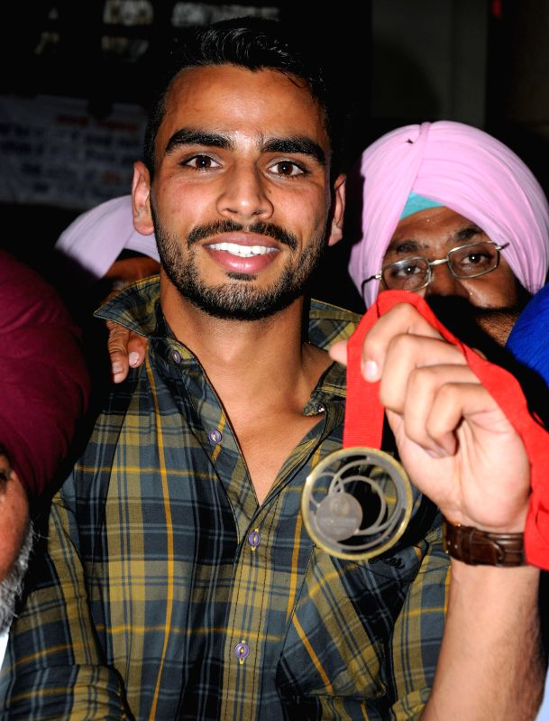 Glasgow Commonwealth Games 2014 bronze medal winner in men`s triple jump event athlete Arpinder Singh is welcomed on his arrival in Amritsar on Aug. 9, 2014.